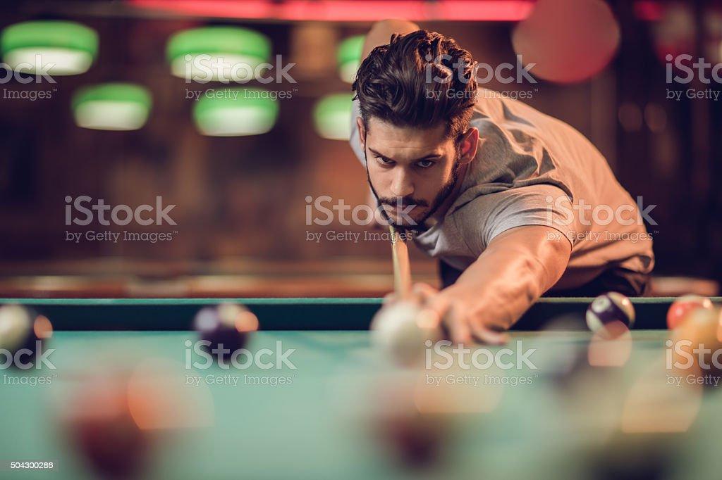 Serious man aiming at pool ball during billiard game. stock photo