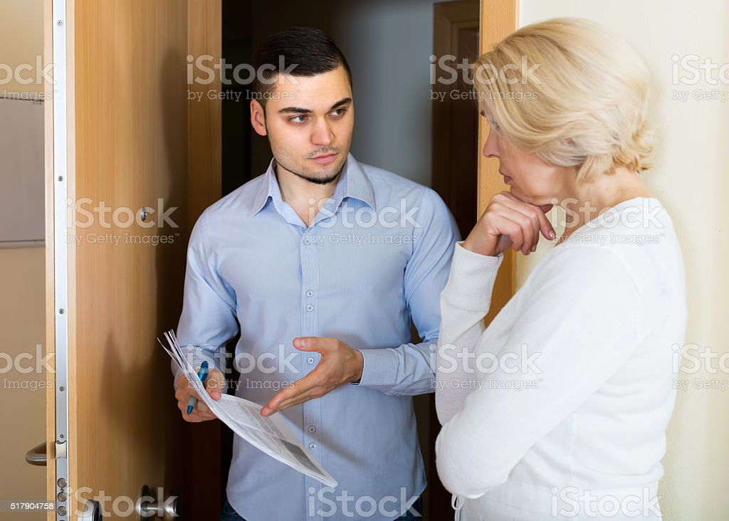 Serious man and housewife at the door stock photo