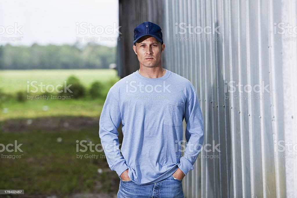 Serious man in cap standing  outside building stock photo