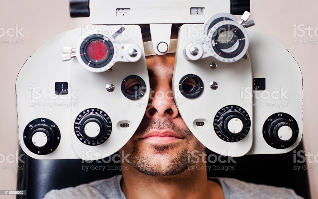 Serious man in phoropter with eye calibration stock photo