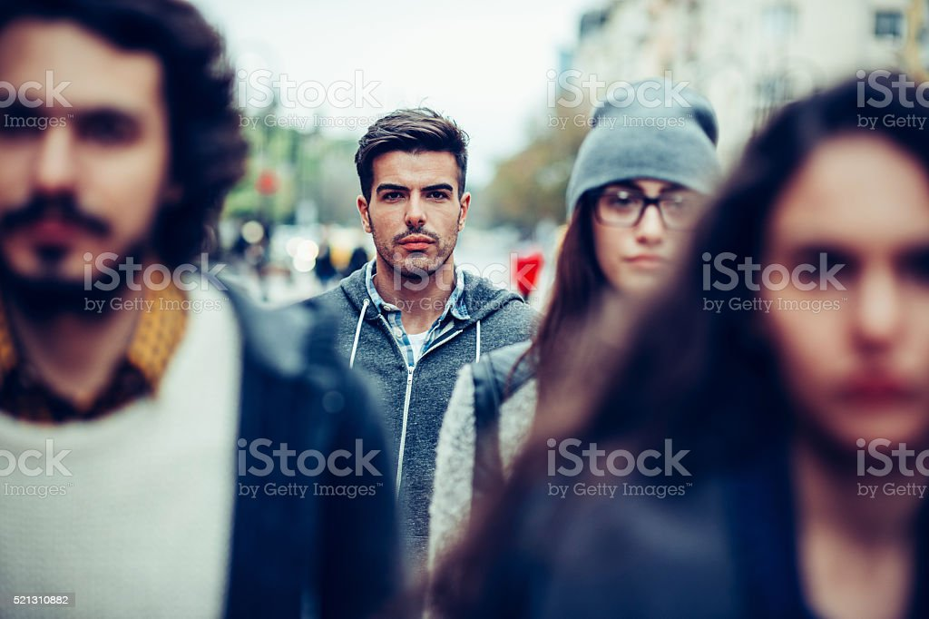 Serious man in the crowd stock photo