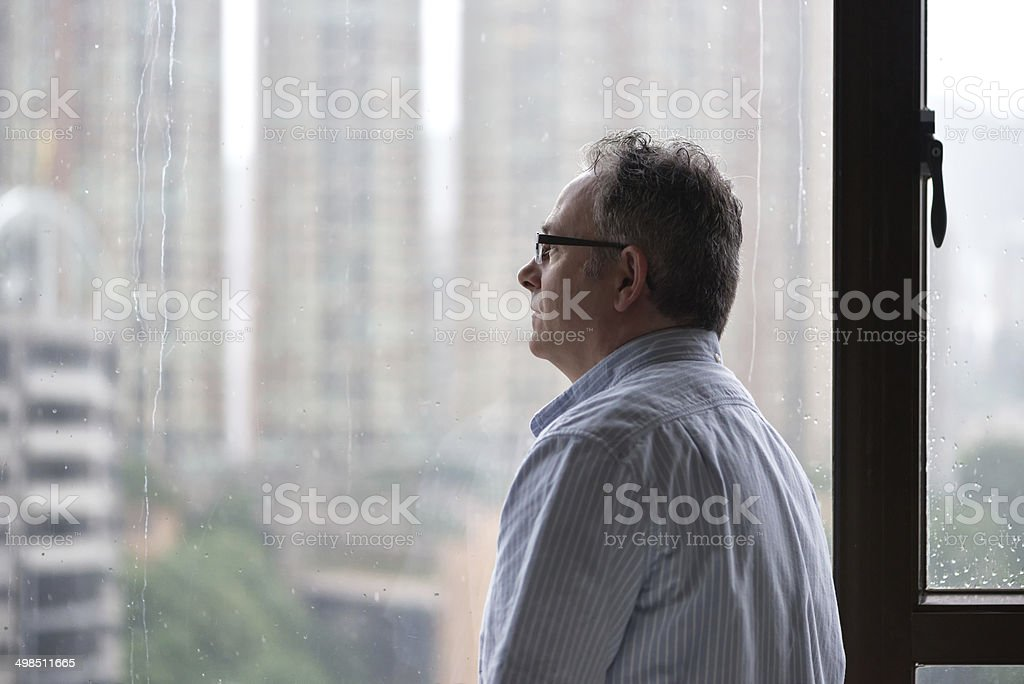Serious Man Looking out Window on Rainy Day stock photo
