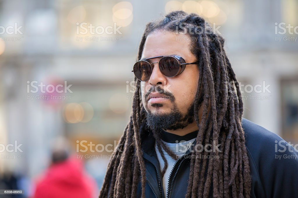 Serious man with dreadlocks. Outdoors portrait stock photo