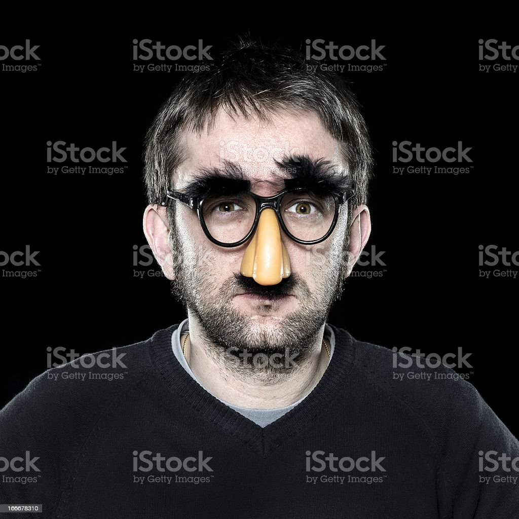 Serious man with fake nose, glasses, moustache and eyebrows stock photo