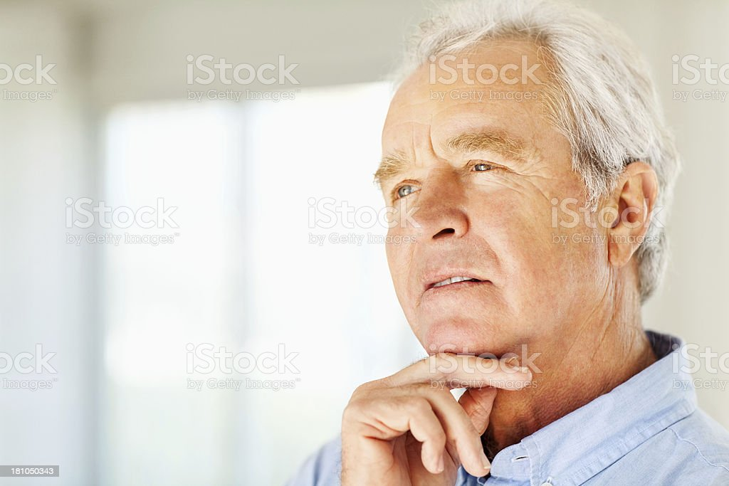 Serious Man With Hand On Chin Looking Away At Home royalty-free stock photo