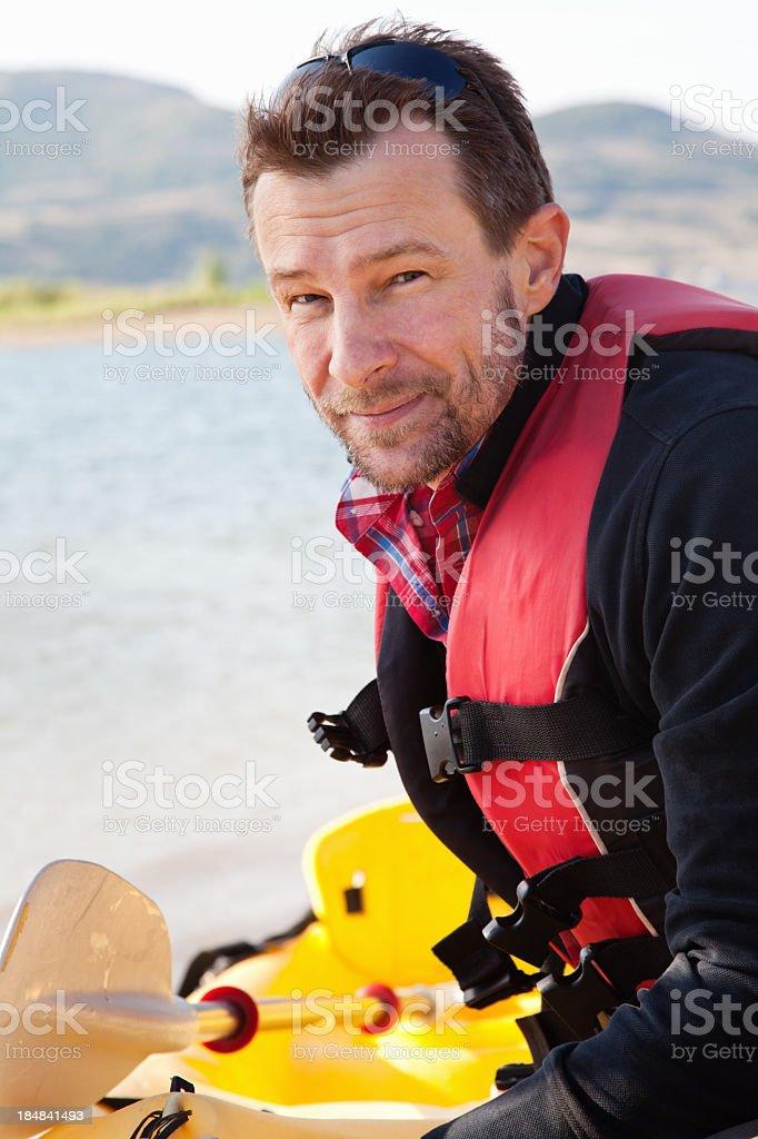 Serious man with his kayak at a lake royalty-free stock photo