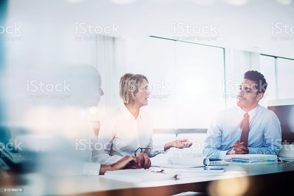 Serious manager discussing with executives at desk stock photo