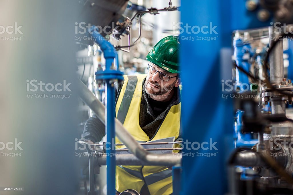 Serious manual worker analysing machine parts at factory stock photo