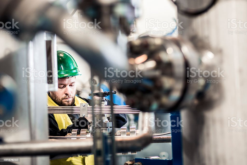 Serious manufacturing professional working at factory stock photo