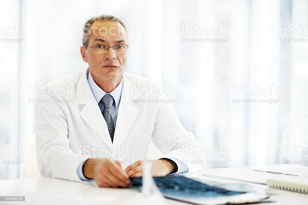 Serious mature doctor sitting in the office. royalty-free stock photo