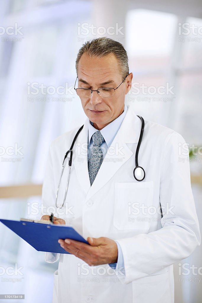 Serious mature doctor writing on medical reports. royalty-free stock photo