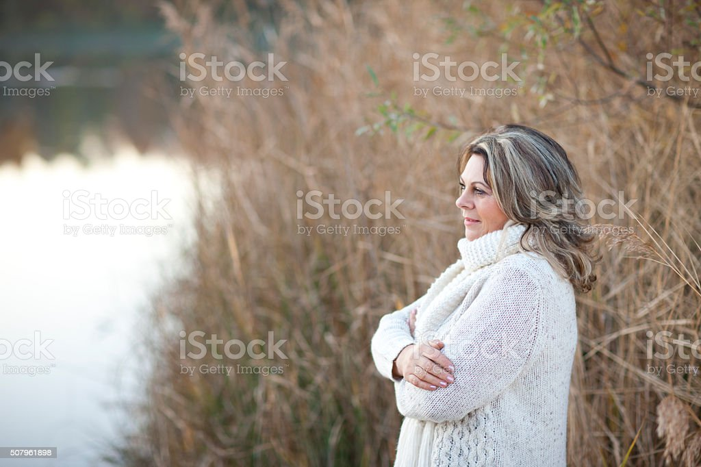 serious matured woman with crossed arms outdoor stock photo