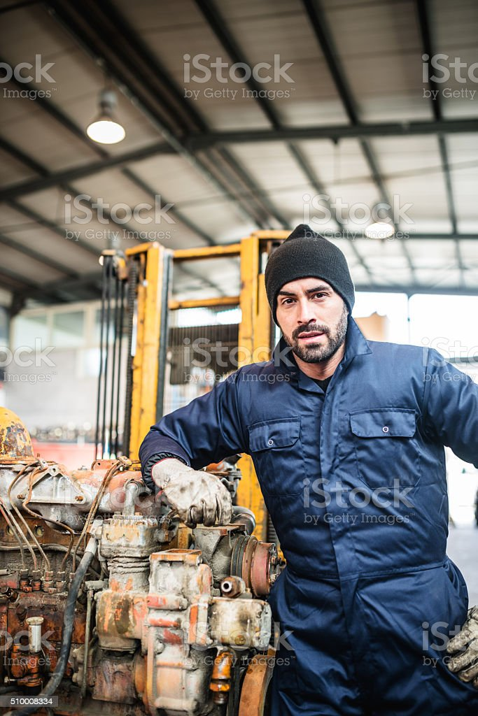 serious mechanic on a garage working on a engine stock photo