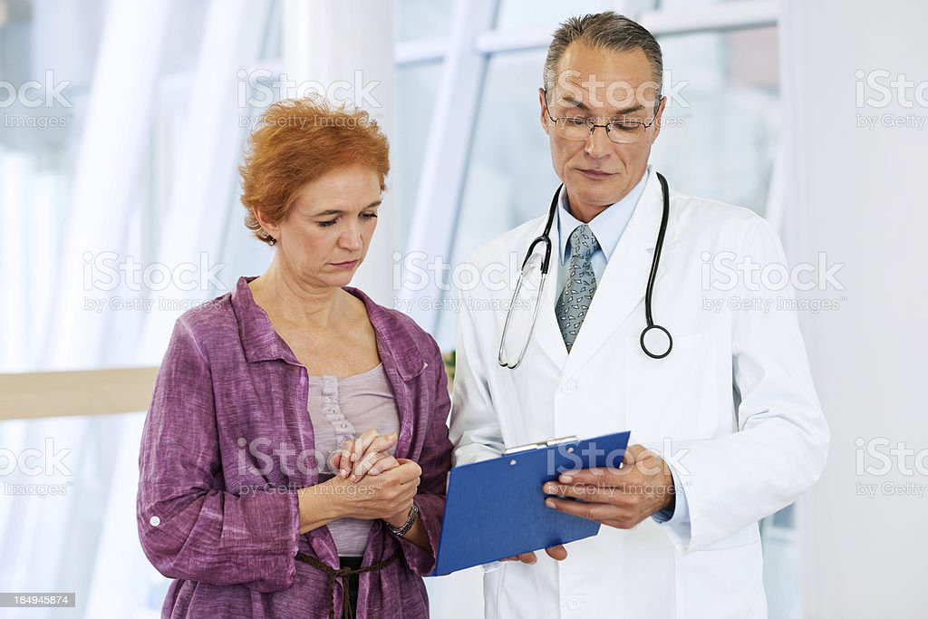 Serious  medical doctor looking  the results wit his patient. royalty-free stock photo