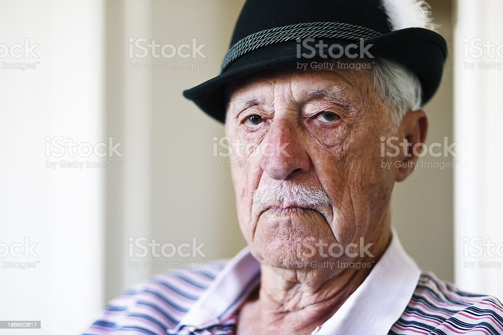 Serious old man in Tyrolean hat stares at camera stock photo