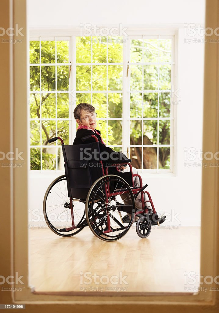 Serious old woman in wheelchair beyond doorway looks over shoulder royalty-free stock photo