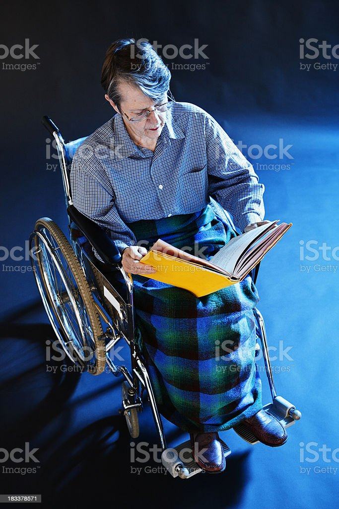 Serious old woman in wheelchair studies book or photo album royalty-free stock photo