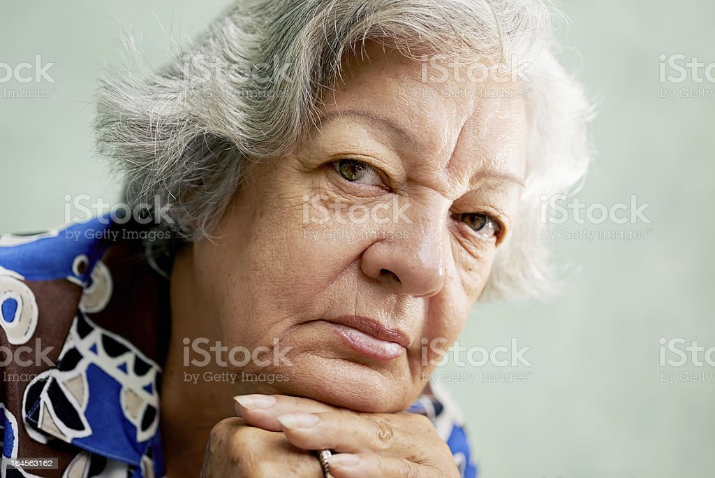 serious old woman looking at camera with hands on chin royalty-free stock photo