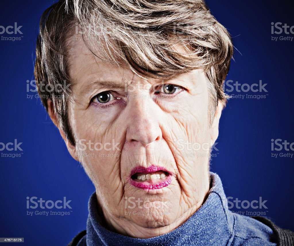 Serious old woman seems doubtful as she challenges something royalty-free stock photo