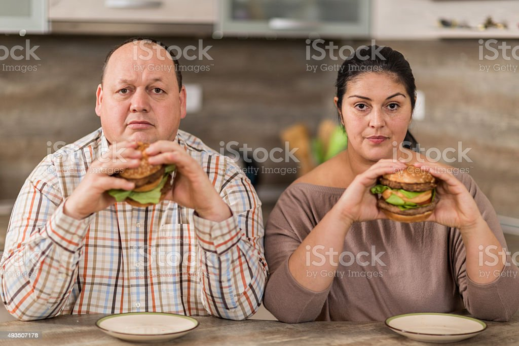 Serious overweight couple eating burgers in the kitchen. stock photo