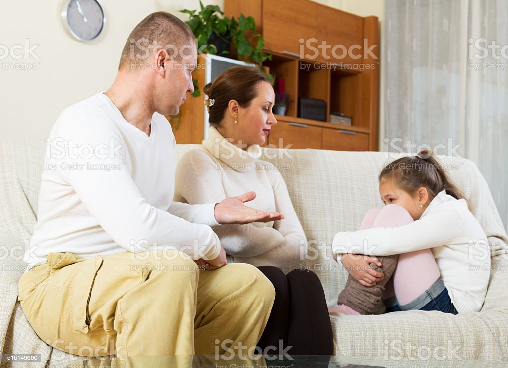 serious parents scolding daughter in home stock photo