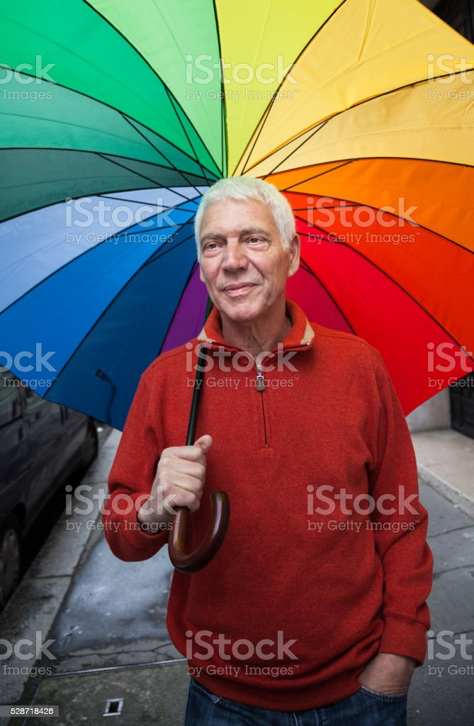 serious pensive senior man walks alone under a rainbow umbrella stock photo