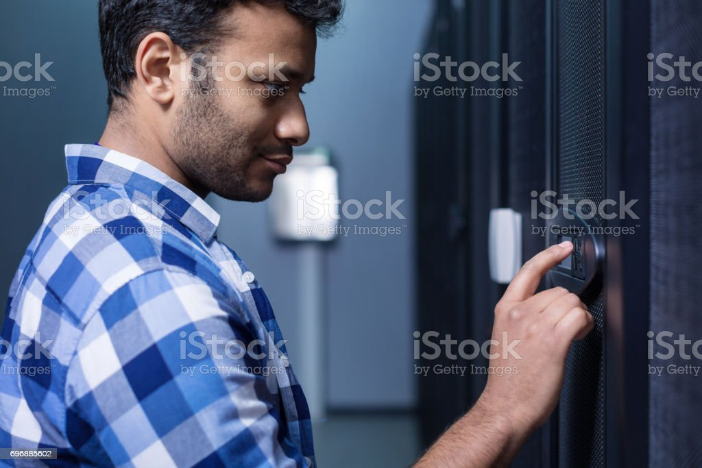 Serious pleasant man looking at the control panel stock photo