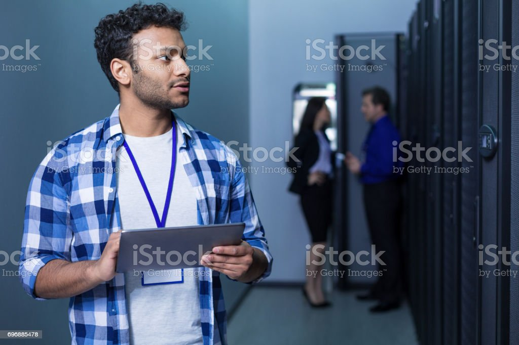 Serious pleasant man working on a tablet stock photo
