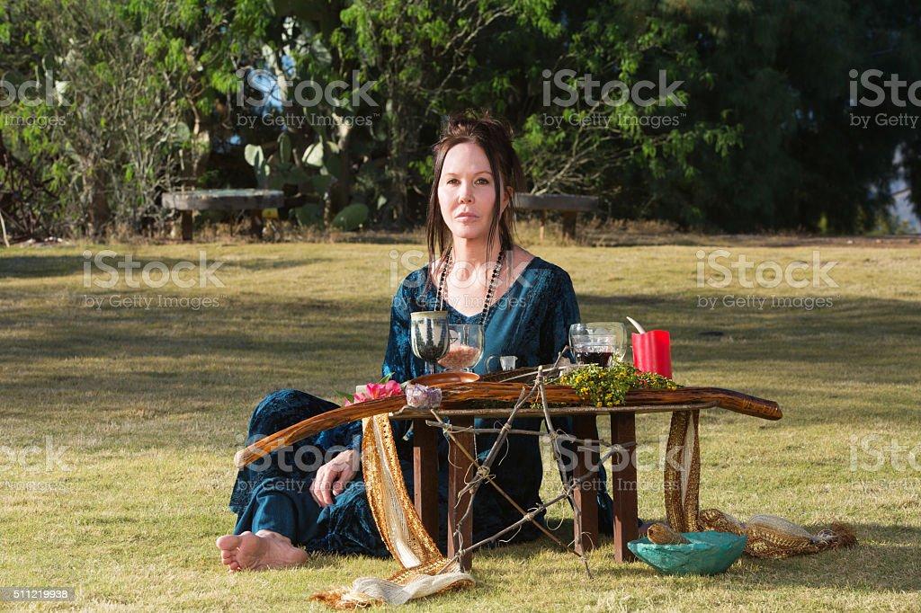 Serious Priestess with Pagan Altar stock photo