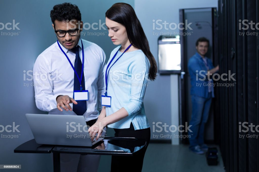 Serious professional colleagues working on the laptop stock photo