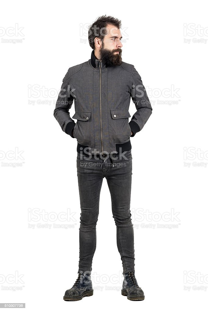 Serious punker in gray jacket, tight jeans and army boots stock photo