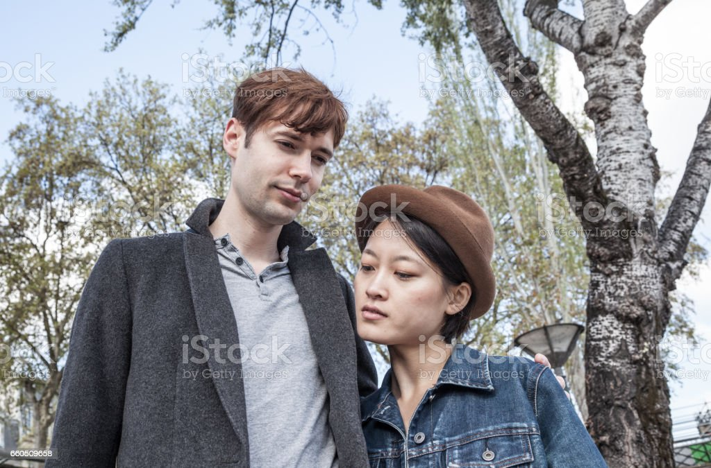 serious quirky Caucasian and oriental multiracial couple share quiet moment  by silver birch tree in springtime paris stock photo