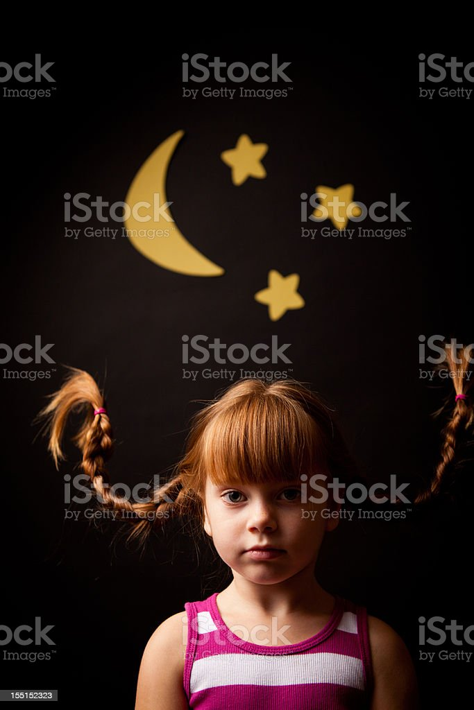 Serious, Red-Haired Girl Wearing Upward Braids With Moon and Stars stock photo