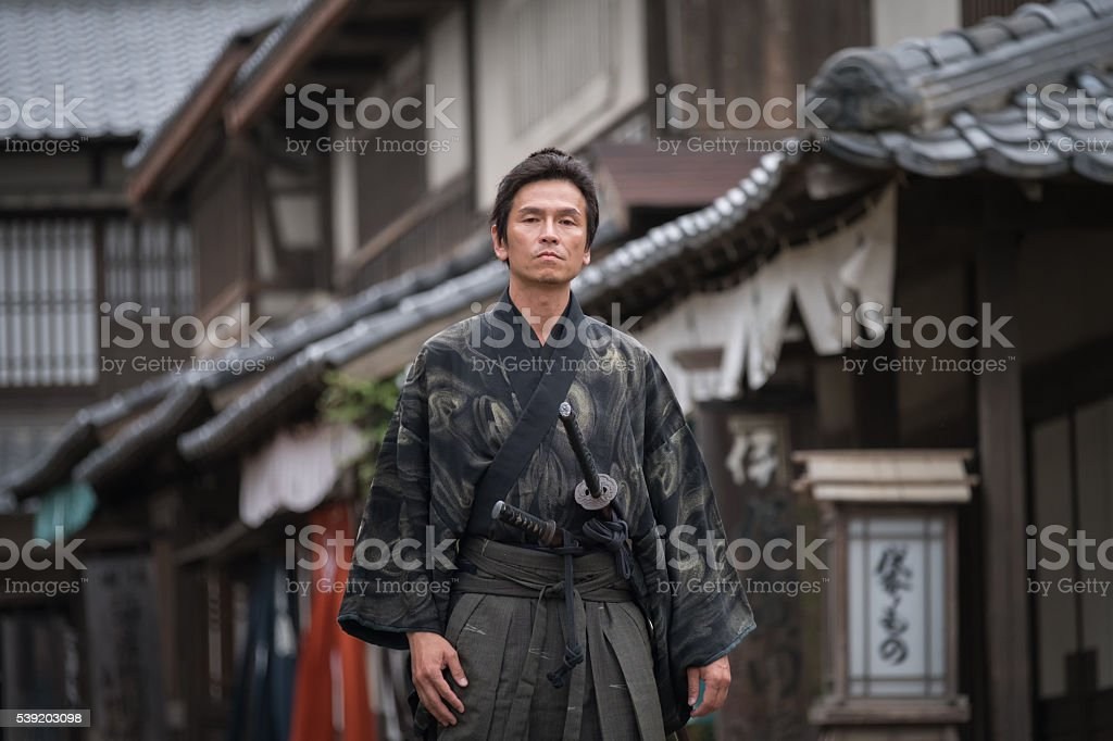 Serious Samurai with Two Swords Walking Down Traditional Japanese Street stock photo