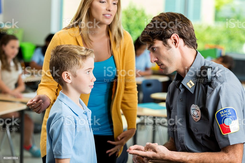 Serious security officer talks with elementary student at school stock photo