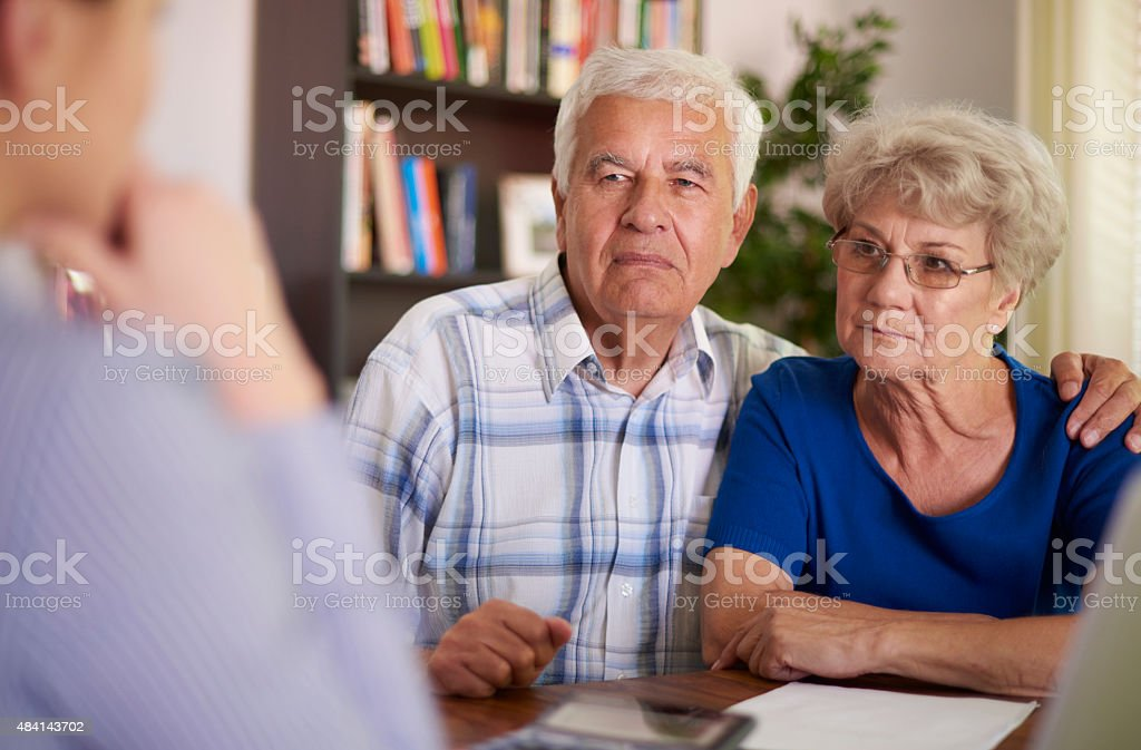 Serious senior couple sitting in the office stock photo