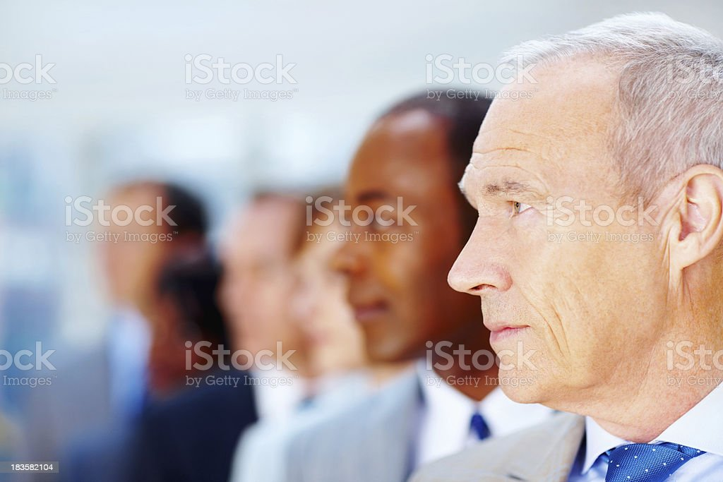 Serious senior executive with team in background royalty-free stock photo
