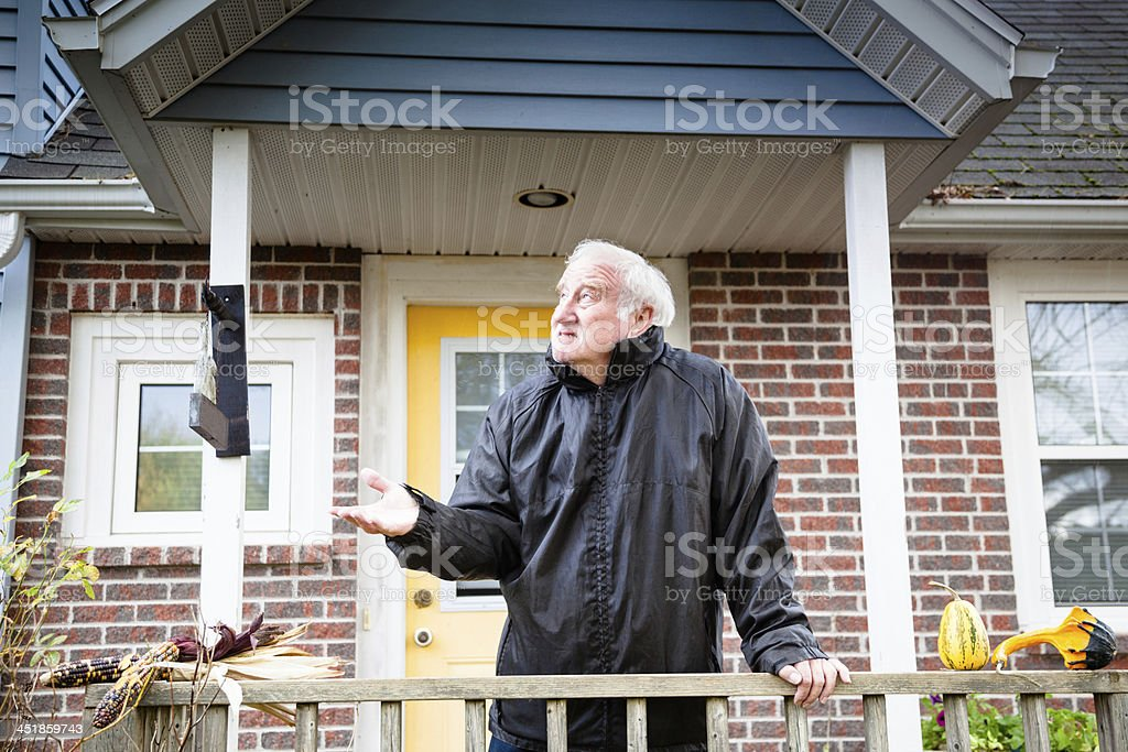 serious senior male checks for rain in house porch royalty-free stock photo