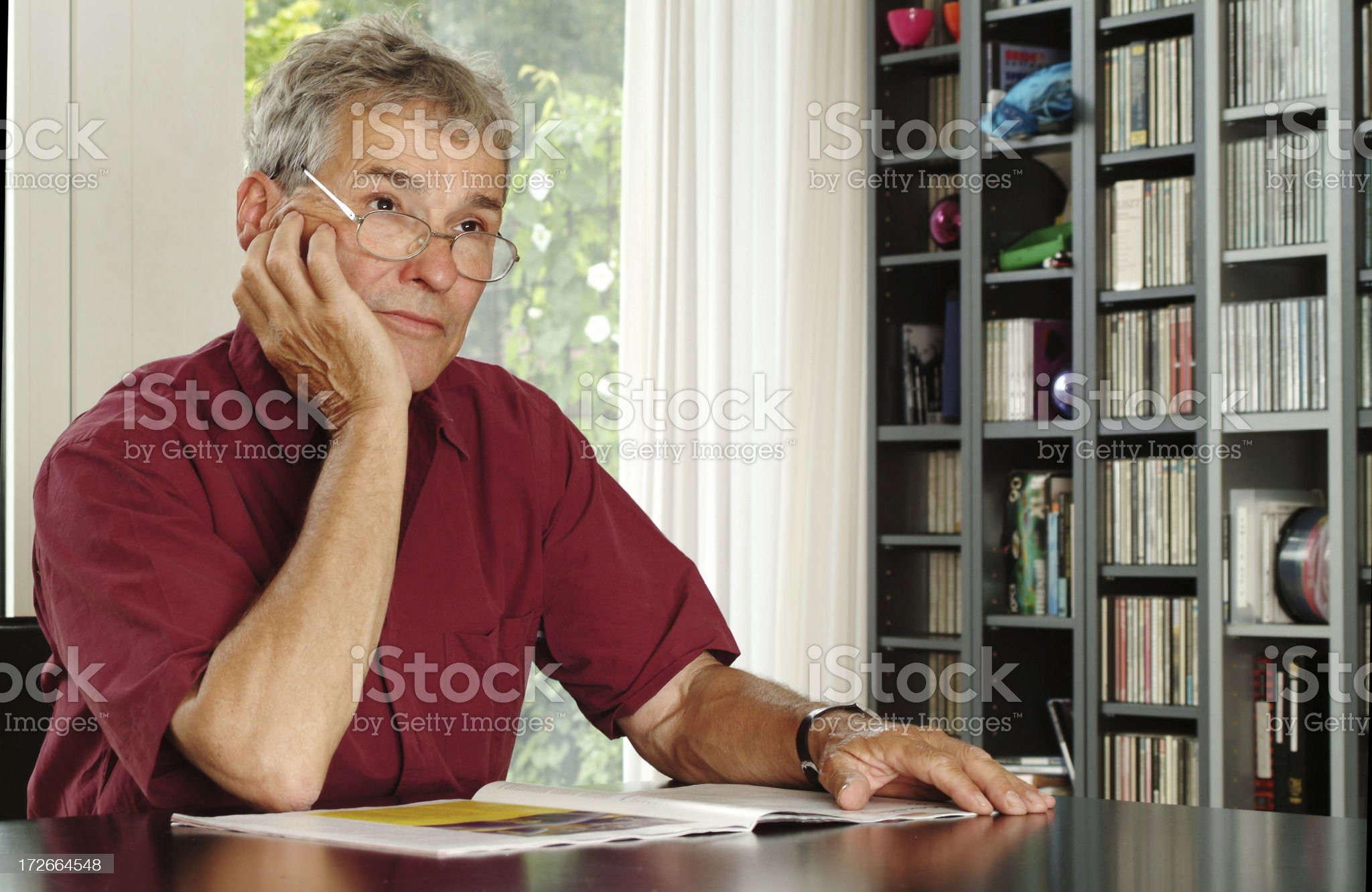 Serious Senior man at table thinking in his living room royalty-free stock photo