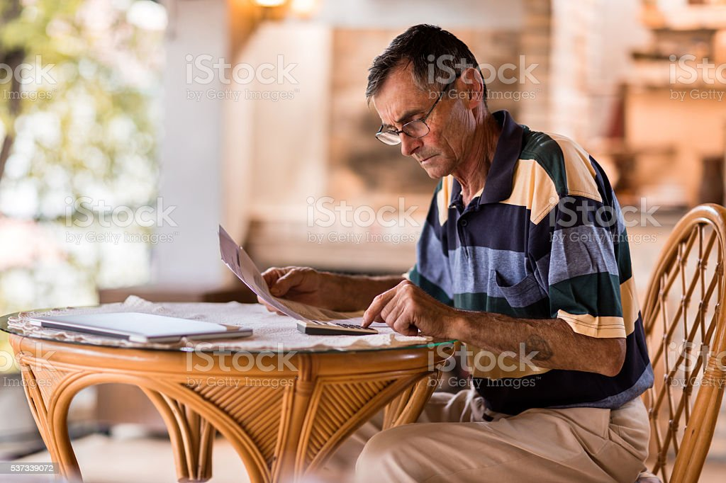 Serious senior man calculating home finances on the terrace. stock photo