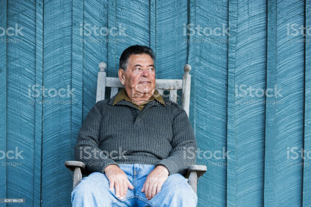 Serious senior man sitting in rocking chair on porch stock photo