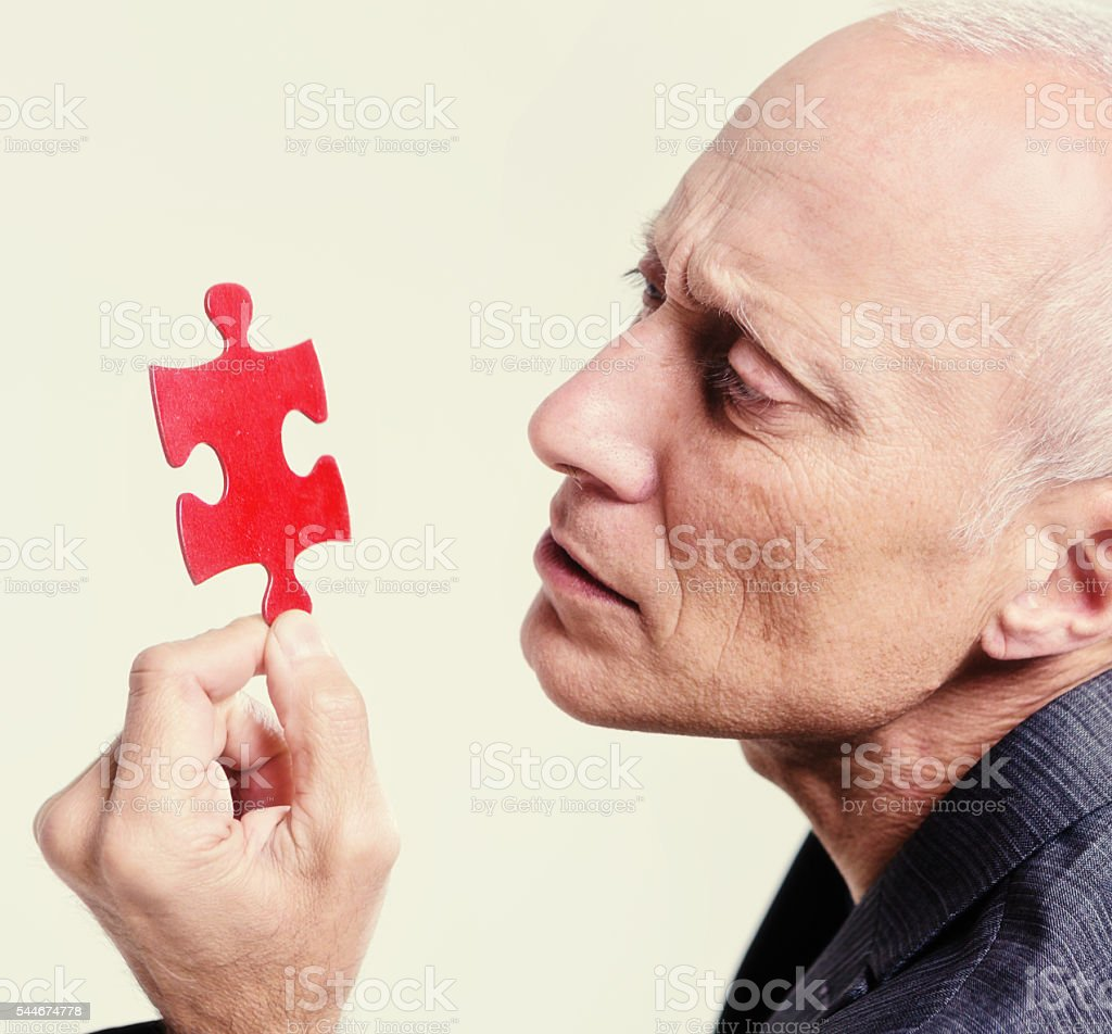 Serious senior man studying red puzzle piece stock photo