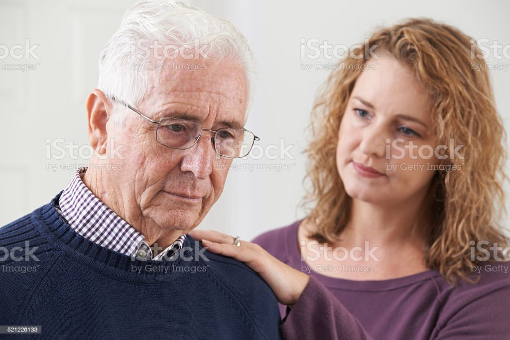 Serious Senior Man With Adult Daughter At Home stock photo