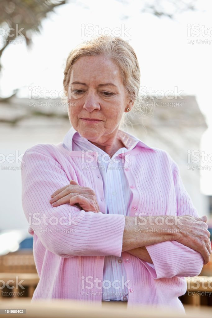 Serious senior woman standing outdoors. stock photo