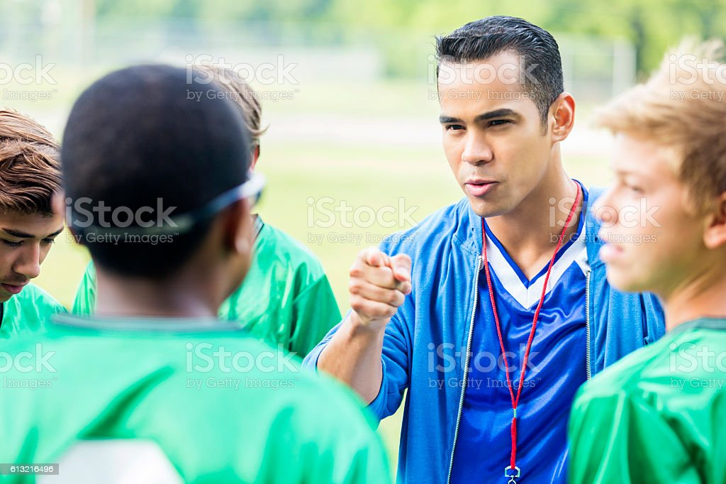 Serious soccer coach motivates his team during time out stock photo