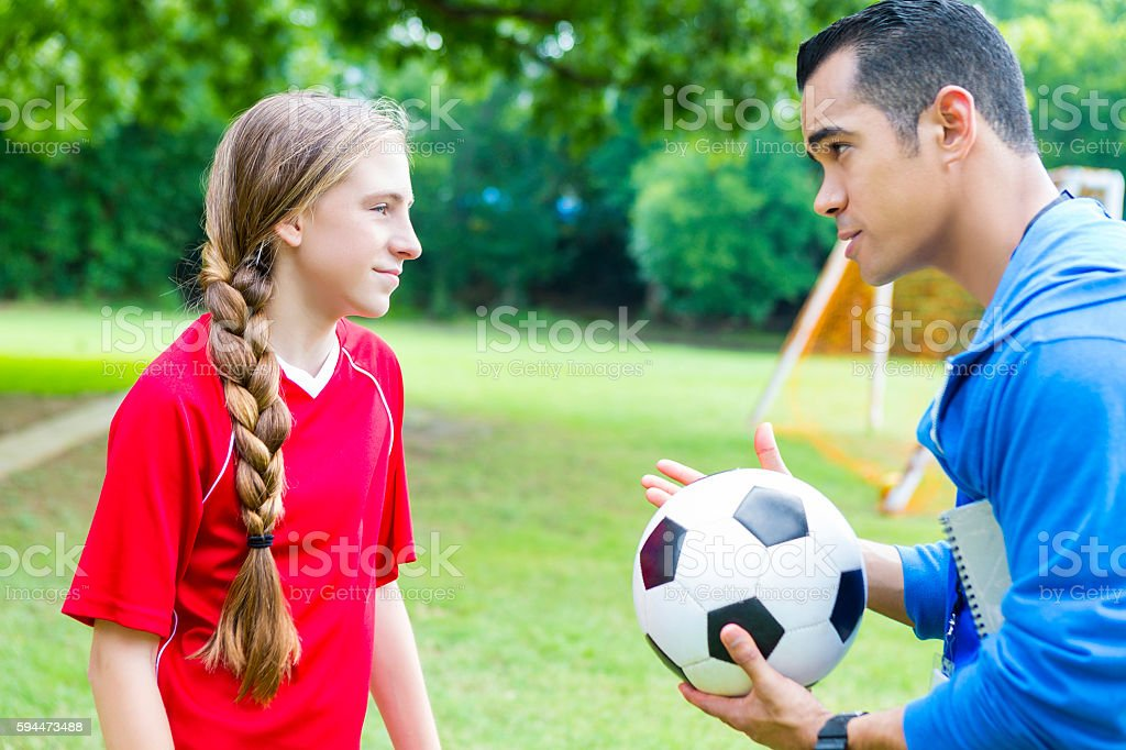 Serious soccer coach talks with player stock photo