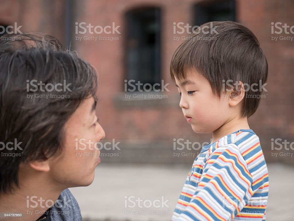 Serious son with father. stock photo