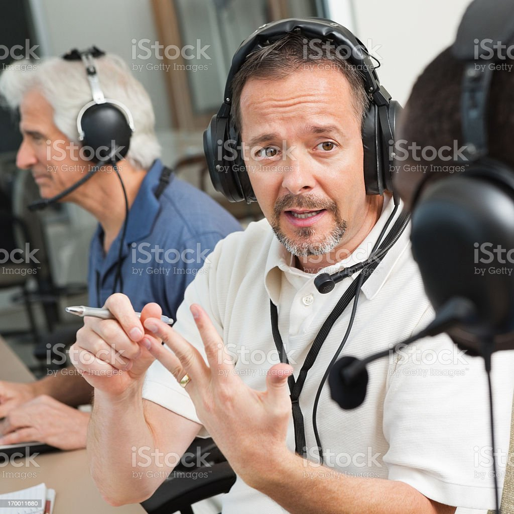 Serious Sports Commentator discussing game in the press box stock photo