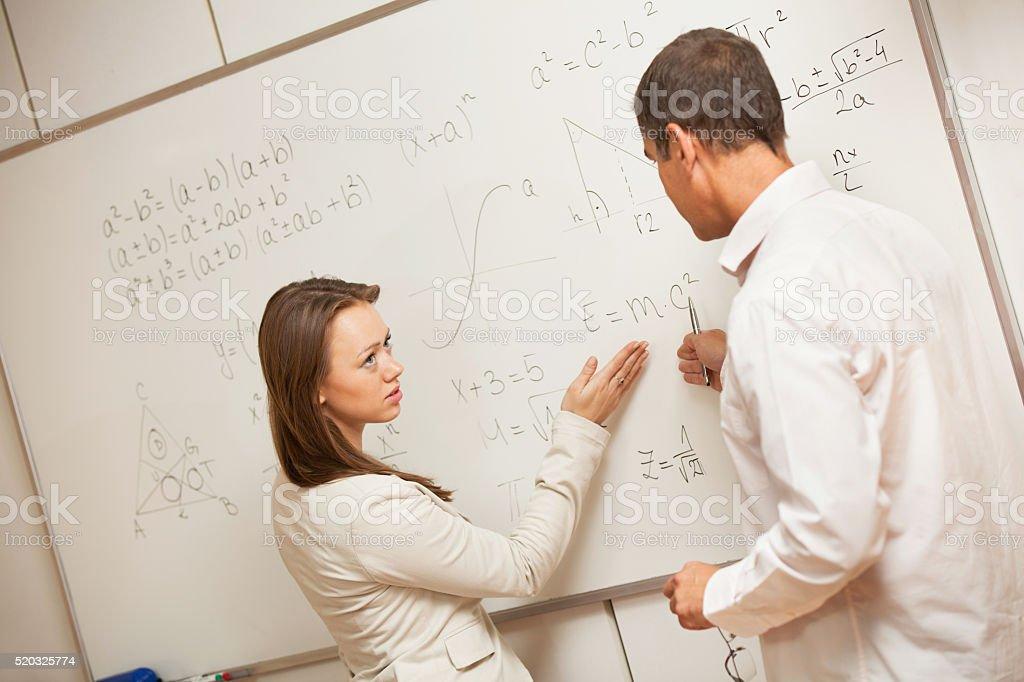 Serious student listening teacher during physics class. stock photo