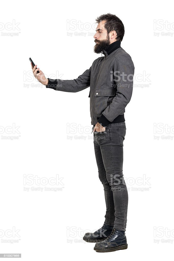 Serious stylish punker in gray jacket taking selfie photo. stock photo